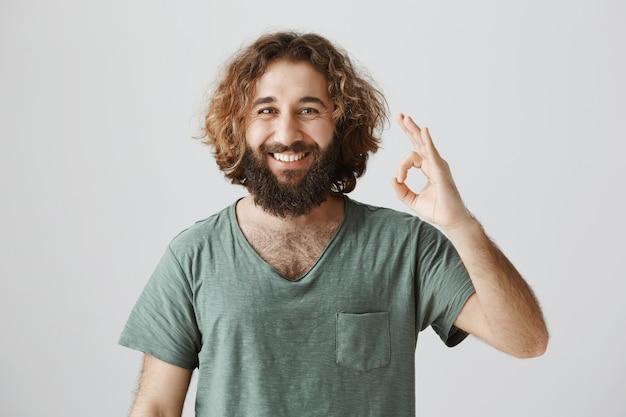 Alegre chico de oriente medio guapo muestra gesto bien, garantía de calidad Foto gratis