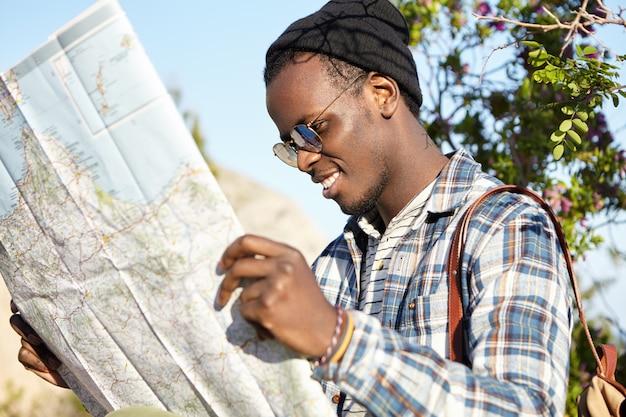 Alegre feliz joven viajero afroamericano con aspecto moderno buscando dirección en el mapa de ubicación, buscando cómo llegar al hotel mientras viaja al extranjero en una ciudad extranjera durante las vacaciones de verano Foto gratis