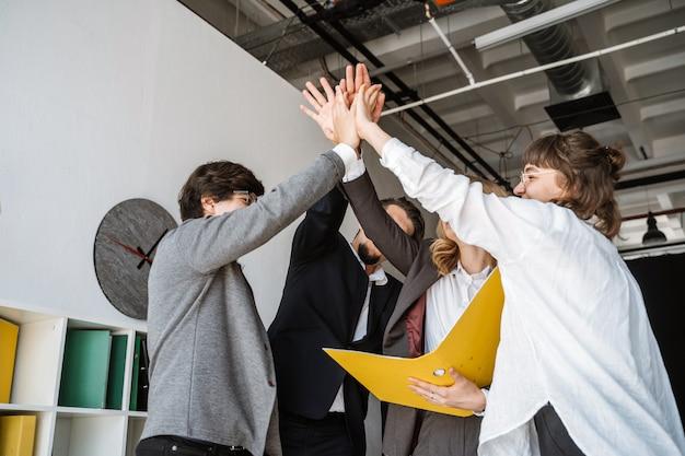 Alegre joven grupo de personas de pie en la oficina y dando choca esos cinco Foto gratis