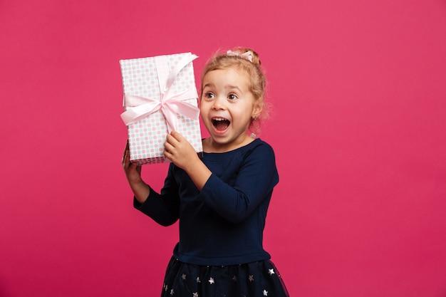 Alegre joven rubia con caja de regalo y se regocija Foto gratis
