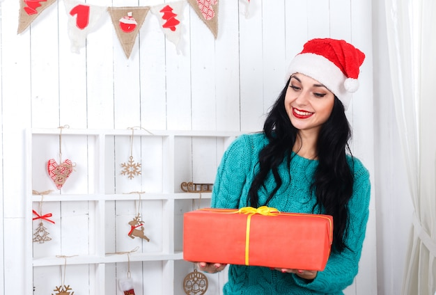 Alegre joven sentada en el interior de año nuevo vestida con sombrero de santa claus con caja de regalo roja. Foto Premium
