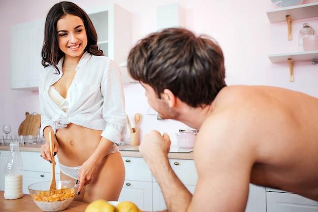 Alegre joven sexy stand en cocina en bikini y camisa. ella descama escamas con leche. modelo mira al hombre y sonríe. guy mírala. Foto Premium
