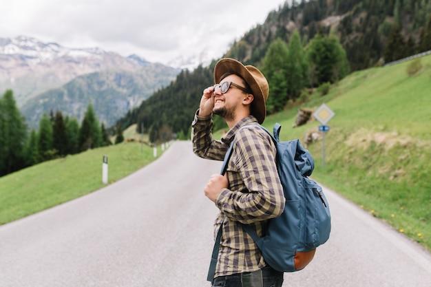 Alegre joven con sombrero marrón claro y camisa a cuadros caminando por la carretera entre campos y hablando por teléfono Foto gratis