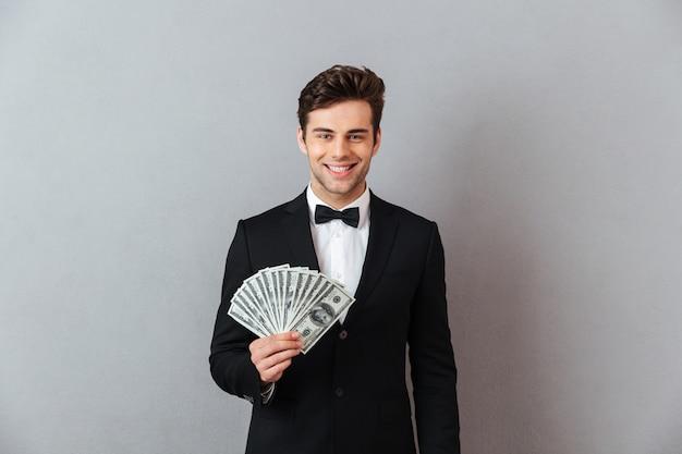 Alegre joven en traje oficial con dinero. Foto gratis