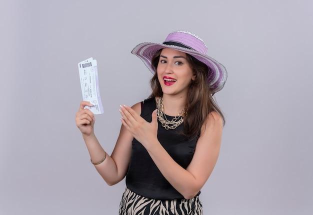 Alegre joven viajera vistiendo camiseta negra con sombrero sosteniendo boletos y apunta a boletos en la pared blanca Foto gratis