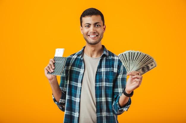 Alegre joven vistiendo camisa a cuadros se encuentran aisladas sobre fondo naranja, sosteniendo billetes de dinero, mostrando el pasaporte con billetes de avión Foto Premium