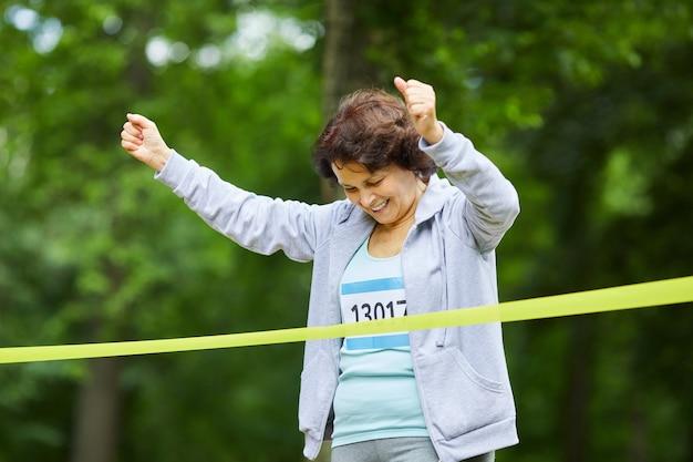 Alegre mujer adulta madura con cabello castaño acabando la carrera de maratón primero, retrato medio, espacio de copia Foto Premium