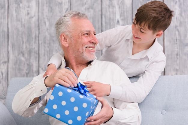 Alegre nieto y abuelo mirándose mientras sostiene la caja de regalo envuelta con lunares azules Foto gratis