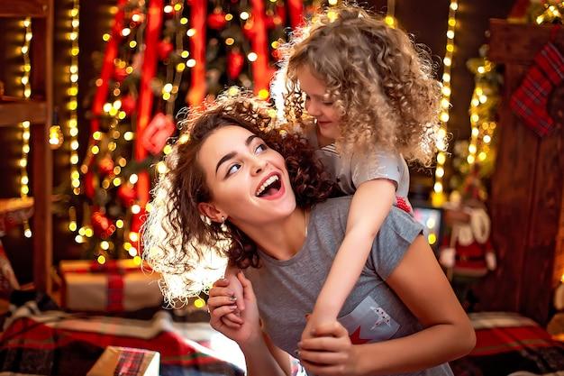Alegre niña rizada linda y su hermana mayor divirtiéndose, abrazando cerca de árbol de navidad en el interior. Foto Premium