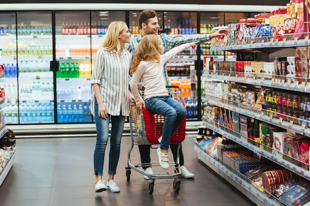 Alegre niña sentada en un carrito de compras Foto gratis