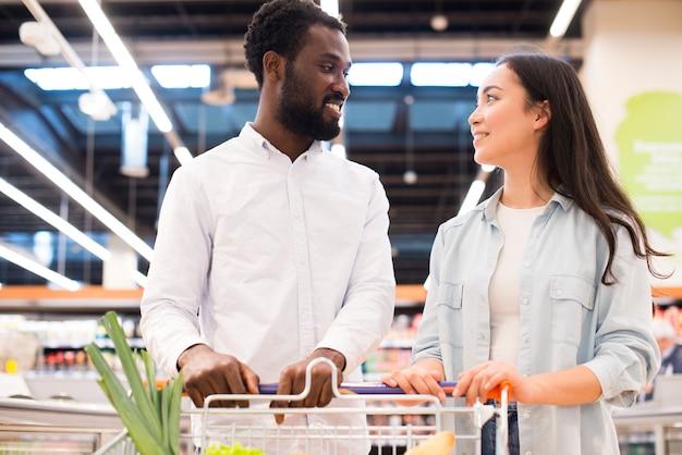 Alegre pareja multiétnica con carrito de compras en el supermercado Foto gratis
