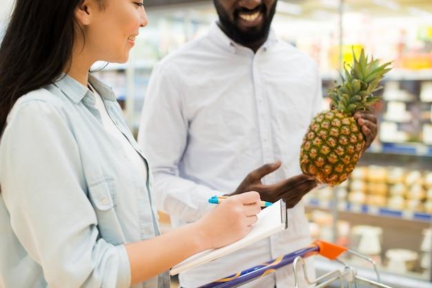 Alegre pareja multiétnica comprando productos en supermercado Foto gratis