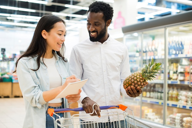 Alegre pareja multirracial comprando productos en supermercado Foto gratis