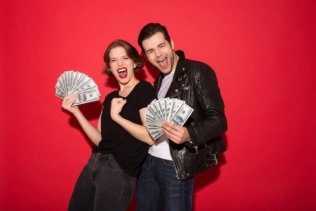 Alegre pareja punk gritando con dinero y mirando Foto gratis
