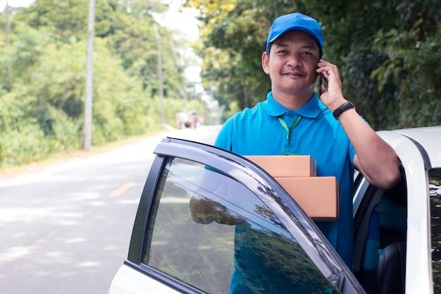 Alegre repartidor asiático sosteniendo una caja y sonriendo mientras está de pie en la carretera Foto Premium