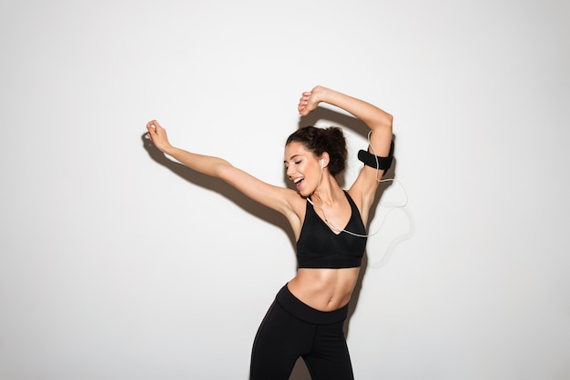 Alegre rizada morena fitness mujer escuchando música por teléfono inteligente Foto gratis