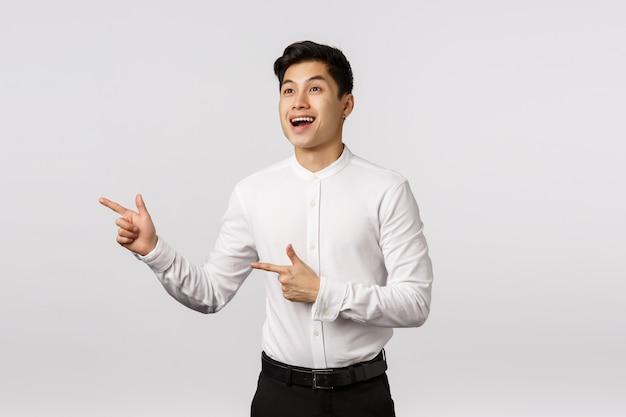 Alegre sonriente joven empresario asiático con camisa blanca apuntando hacia el lado Foto Premium