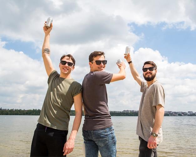 Alegres amigos levantando manos con cerveza Foto gratis