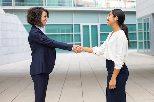 Alegres colegas estrechándole la mano cerca del edificio de oficinas. mujeres jóvenes con trajes formales reunión al aire libre. concepto de apretón de manos de negocios Foto gratis