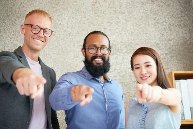 Alegres colegas multiétnicos de pie en la oficina y apuntando hacia la cámara Foto gratis
