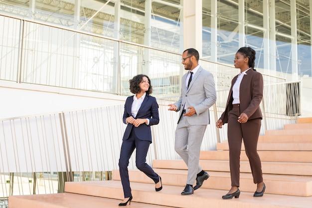 Alegres colegas de negocios caminando en el edificio de oficinas Foto gratis