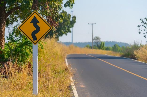 Alerta de tráfico cuesta abajo. reduzca la velocidad y use una marcha más baja. señal de tráfico de flecha con cielo azul. señal de advertencia en la calle. Foto Premium