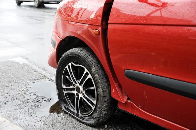Aleta delantera izquierda y rueda del accidente automovilístico rojo Foto Premium