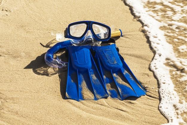 Aletas de natación azul, máscara, snorkel para practicar surf en la playa de arena. concepto de playa Foto Premium