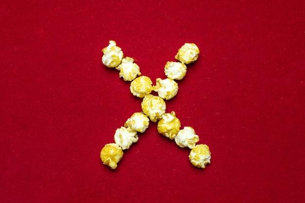 Alfabeto inglés del cine palomitas. letra x. fondo rojo para diseño. Foto Premium