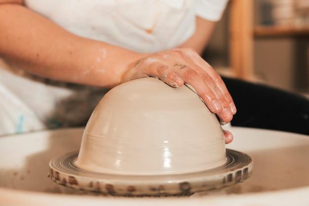 Alfarero profesional haciendo bol en taller de alfarería. Foto gratis