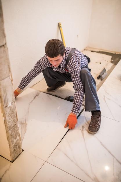 El alicatador del trabajador de la construcción es azulejos, adhesivo para pisos de baldosas de cerámica. colocación de baldosas cerámicas. Foto gratis