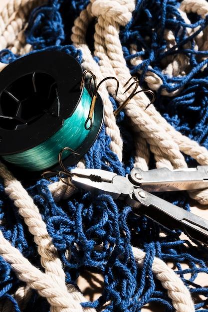 Alicates y ganchos de pesca en red de pesca azul Foto gratis