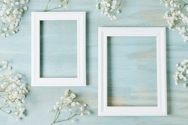 El aliento del bebé blanco florece alrededor del marco blanco de madera vacío sobre un fondo de textura azul Foto gratis