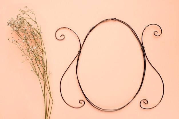 El aliento del bebé florece cerca del marco ovalado vacío sobre un fondo de color melocotón Foto gratis