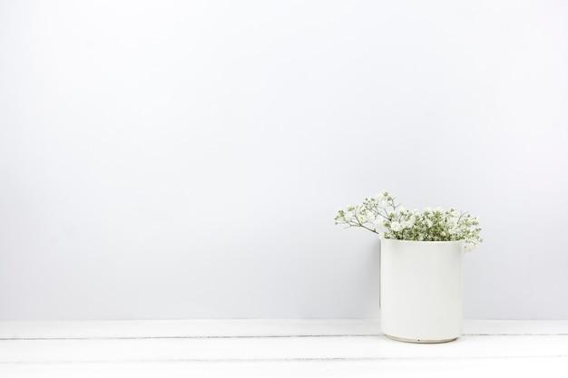El aliento del bebé florece en un jarrón de cerámica sobre una mesa de madera blanca. Foto gratis