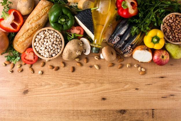 Alimentación saludable. dieta mediterránea. frutas, verduras, granos,  nueces, aceite de oliva y pescado en la mesa de madera vista superior  copyspace | Foto Premium