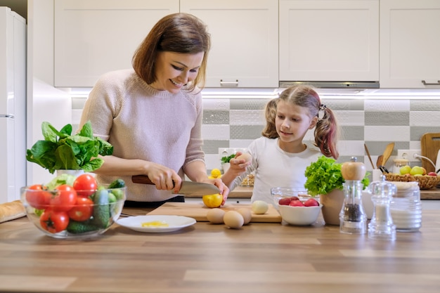 Una alimentación saludable, la madre enseña a la hija a cocinar Foto Premium