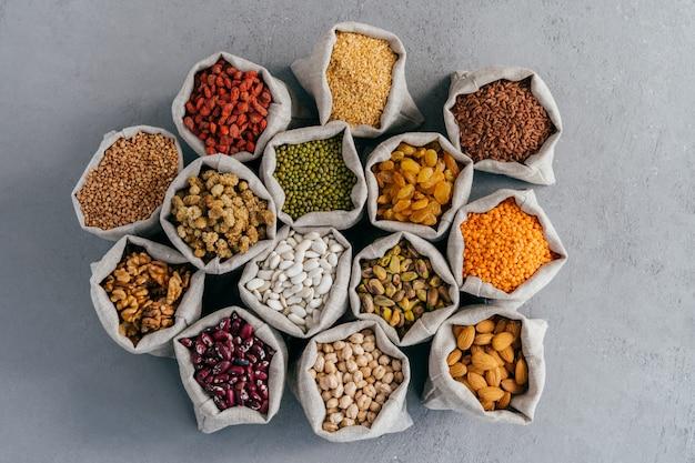 Alimentos crudos de grano saludable y legumbres. bolsas de cereales y frutas secas de arpillera. Foto Premium