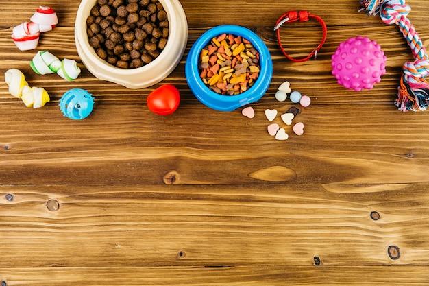 Alimentos para mascotas y juguetes en superficie de madera. Foto gratis