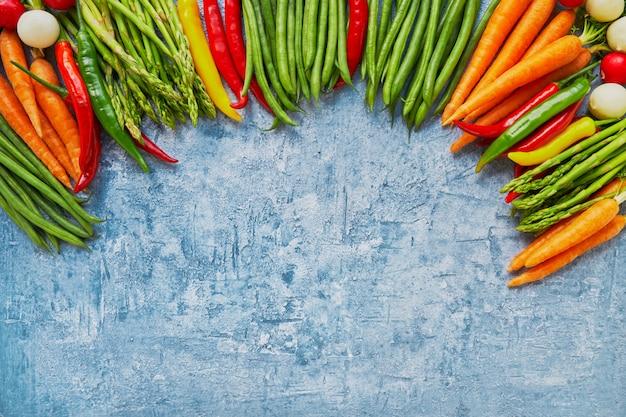 Alimentos orgánicos. capítulo de verduras coloridas en fondo azul brillante. Foto Premium