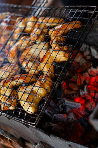 Alitas de pollo a la parrilla en una red de la parrilla sobre el carbón rojo para la fiesta del patio trasero. Foto Premium