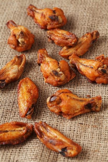 Alitas de pollo a la parrilla sobre un mantel de lino Foto gratis