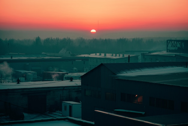 Almacenamiento de mercancías en almacenes en invierno al amanecer. vista desde arriba del área industrial en la salida del sol en tonos rosados. zona de edificios industriales de cerca con copyspace. Foto Premium