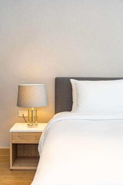 Almohada blanca en la cama con lámpara de luz Foto gratis