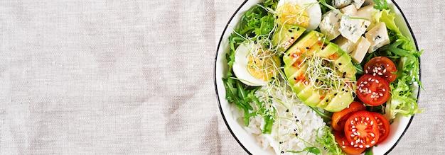 Almuerzo vegetariano verde saludable tazón de buda con huevos, arroz, tomate, aguacate y queso azul en la mesa. Foto gratis