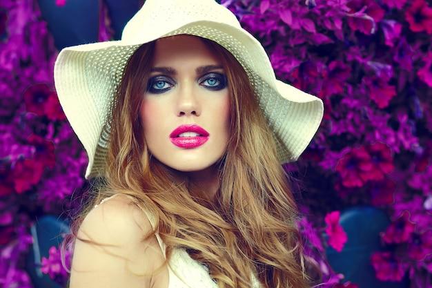 Alta moda look.glamor closeup retrato de hermosa sexy elegante rubia joven modelo con maquillaje brillante y labios rosados con piel limpia perfecta en sombrero cerca de flores de verano Foto gratis