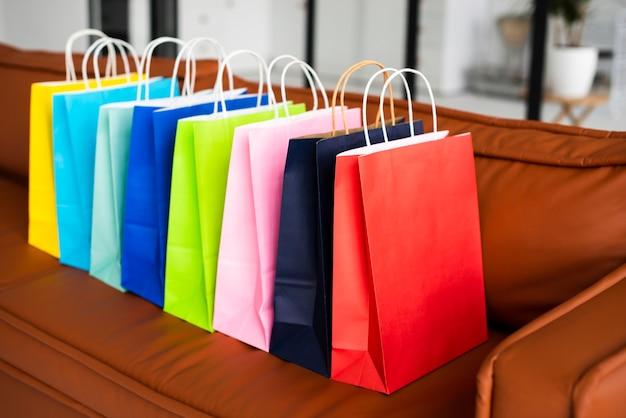 Alta vista de coloridas bolsas de papel en el sofá Foto gratis