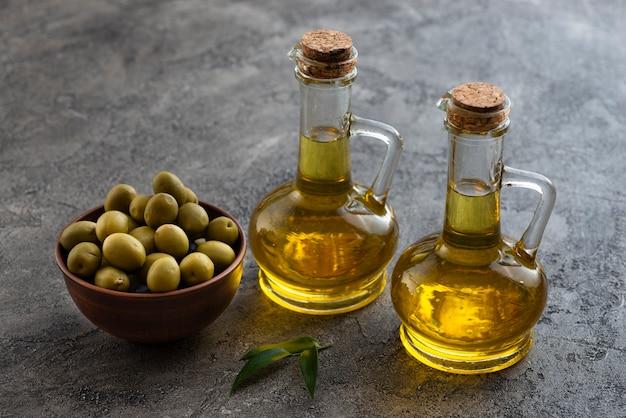 Alta vista de lindas botellas de aceite de oliva y un tazón de aceitunas Foto gratis