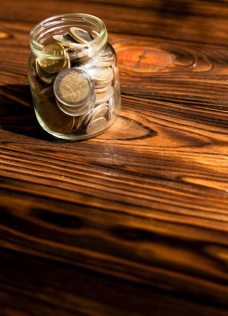 Alta vista monedas en un frasco sobre fondo de madera Foto gratis