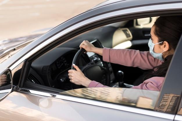 Alta vista mujer con máscara médica y conducir Foto gratis